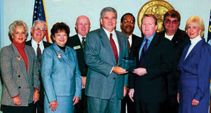 Education Award - Lanny Wilson, Commission Chairman, (r) receives ARELLO award from Larry Outlaw, Director, Education and Licensing. Commission members (l. to r.) are Marsha lordan, Raymond Bass Wanda Proffitt, William Lackey, Sang Hamilton, Allan Dameron and Mona Hill.